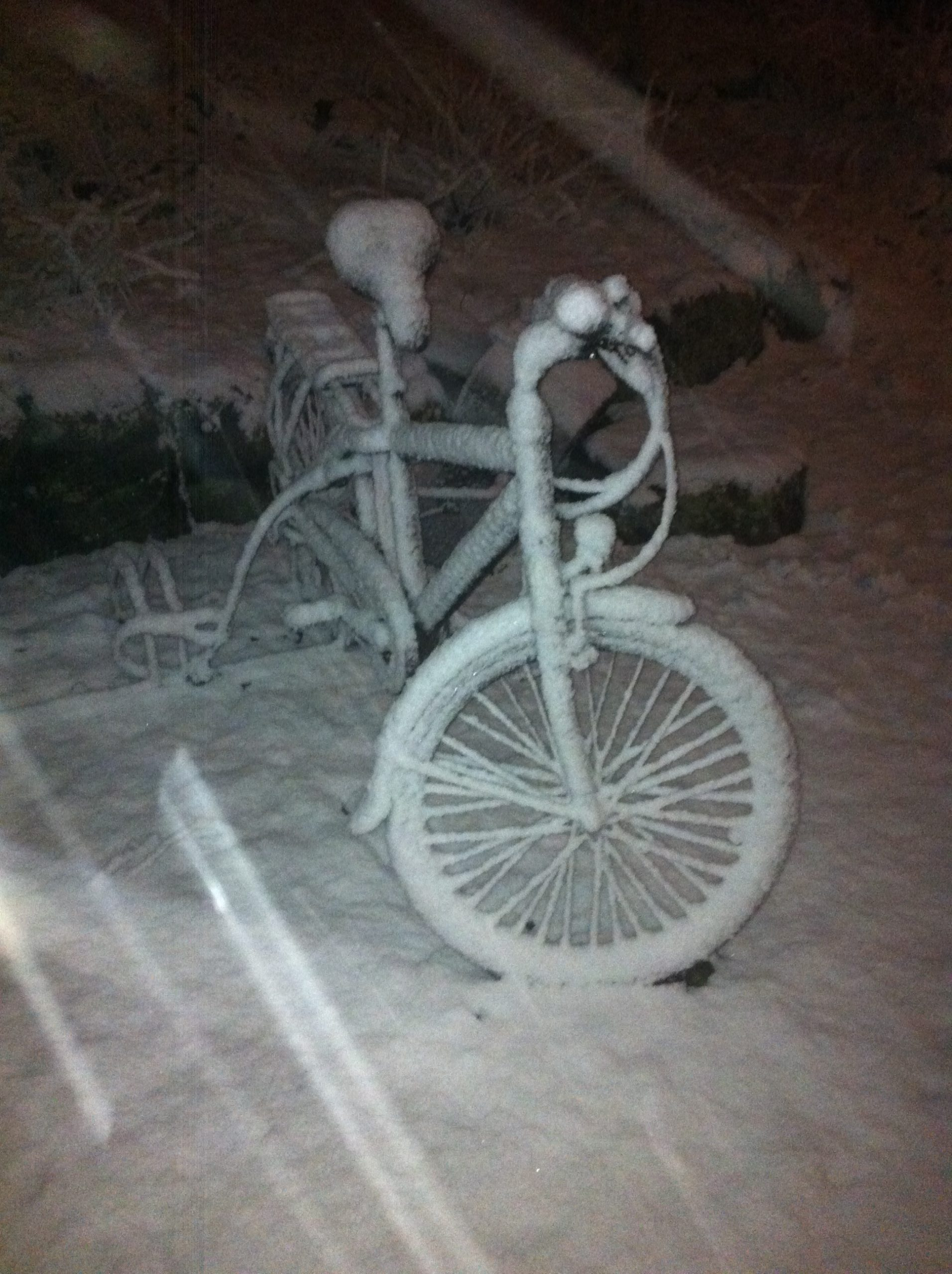 A bicycle painted white of snow