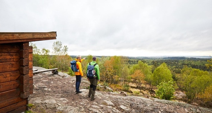 Two trekkers gazeing over a forest view